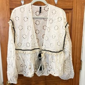 Open blouse with ruffles and pom poms